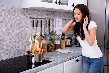 young woman looking at burning cooking