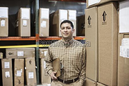 a hispanic male warehouse worker standing
