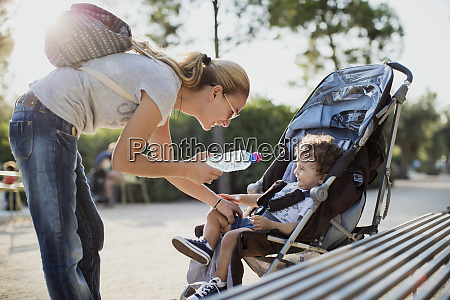 mother giving water bottle to his