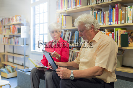 senior couple with laptop and book