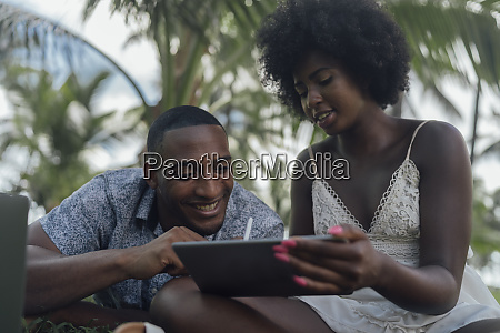 young woman showing tablet to boyfriend
