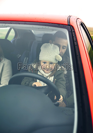 little girl with wool cap driving