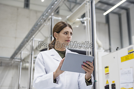 woman checking manufacturing machines in high