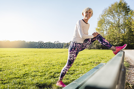 smiling senior woman stretching on a