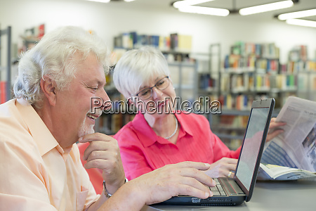 senior couple with laptop and newspaper