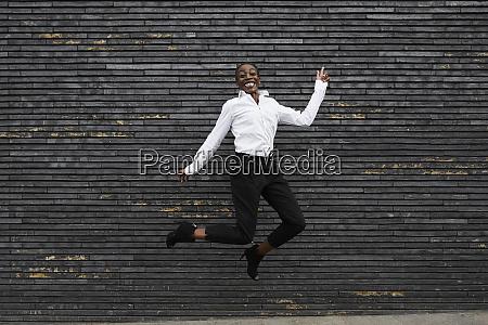 grinning mujer de negocios saltando en
