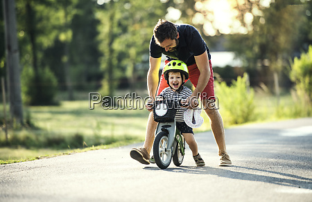 father teaching little son riding bicycle