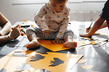 baby girl painting halloween decoration at