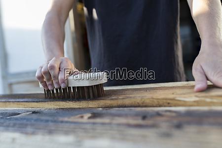 artesana usando cepillo en pedazo de