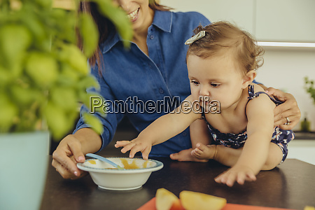 mother with baby daughter eating fruit