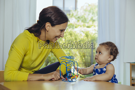 happy mother and baby daughter playing