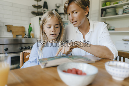 mother and daughter reading book at