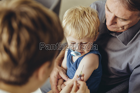 father holding son while being vaccinated
