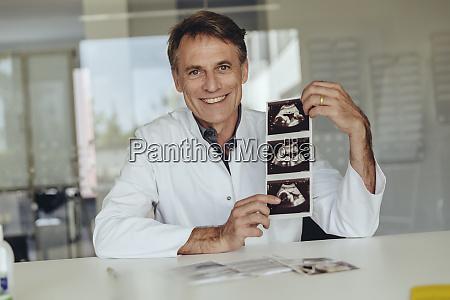 doctor sitting at desk showing ultrasound
