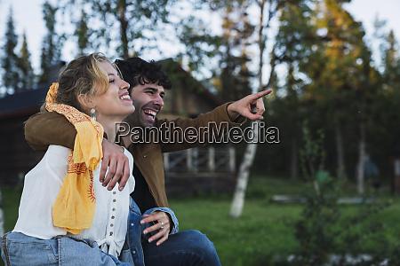 happy couple sitting on bench man
