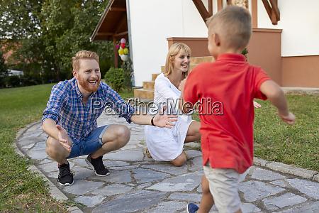 boy running towards happy parents on