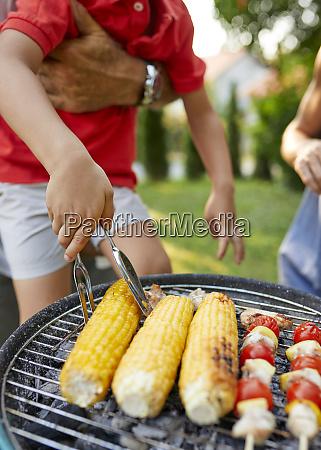 boy turning a corn cob during