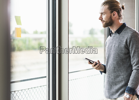 young businessman with cell phone looking
