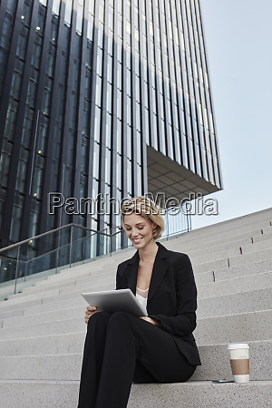 blond businesswoman with coffee to go