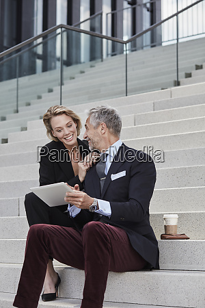 two smiling business people with tablet