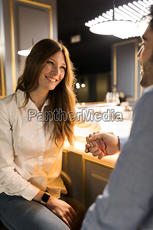 smiling woman holding hands with man
