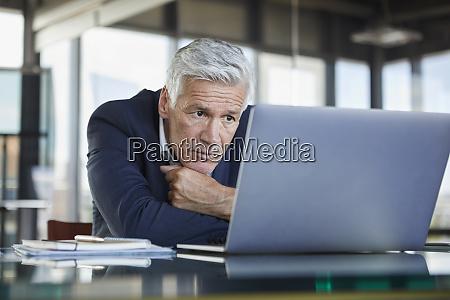 empresario sentado en el escritorio tratando