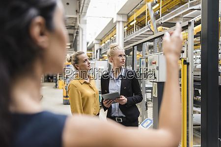 women with tablet talking in modern