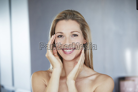 portrait of smiling blond woman touching