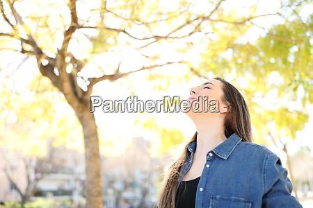 mujer relajada esta respirando aire fresco