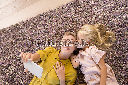 smiling mother and daughter lying on