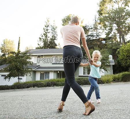 mother playing with daughter in front