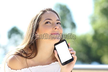 pensive girl showing blank phone screen