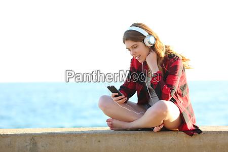feliz adolescente mujer escuchando musica desde