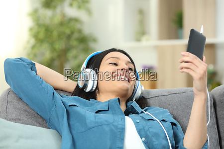 mujer feliz en un sofa escuchando