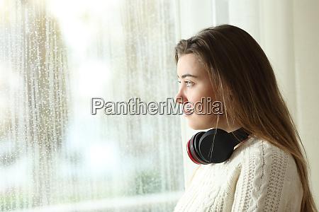 triste adolescente con auriculares mirando a
