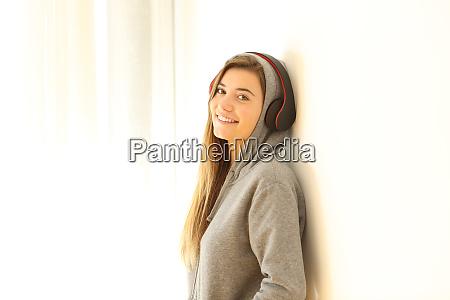 adolescente posando escuchar musica usando auriculares