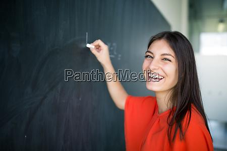 bonita joven universidad estudiante escritura pizarra