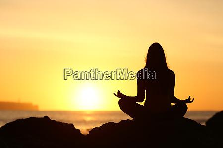 silueta de mujer haciendo yoga al