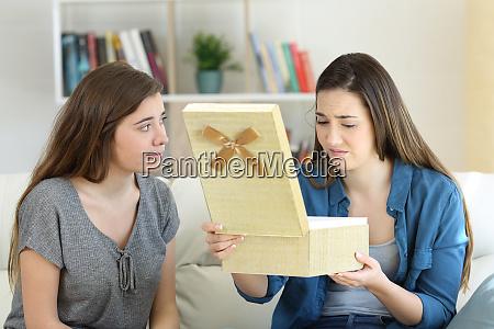 chica decepcionada abriendo un regalo al