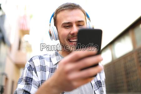 hombre feliz escuchando musica comprobando el