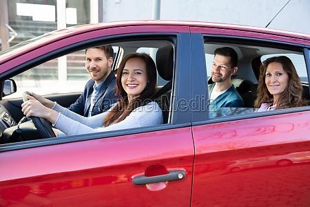 gente sonriente sentada en el coche