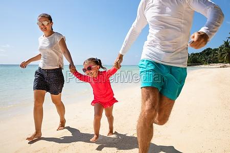 familie gluecklich strand kind laechelnd laufen