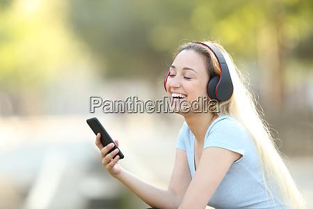chica feliz escuchando musica con auriculares