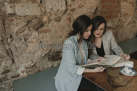 two young women with notebook and