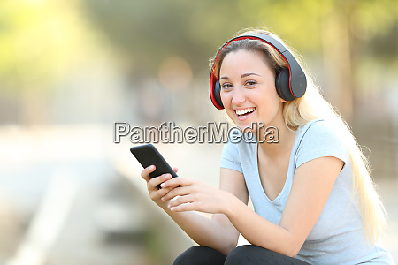 chica adolescente feliz escuchando musica mirando