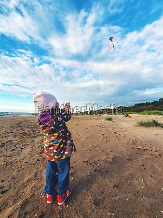 little child flying a kite in