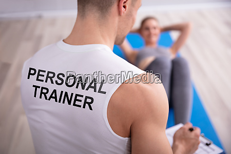 personal trainer looking at woman doing
