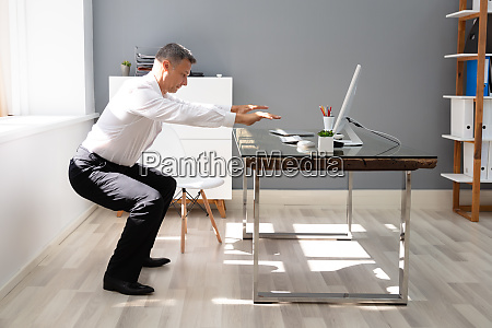 businessman doing squats exercise in office