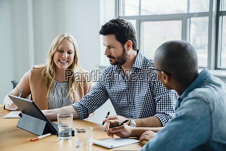 coworkers using digital tablet in board