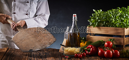 chef holding a wooden paddle in
